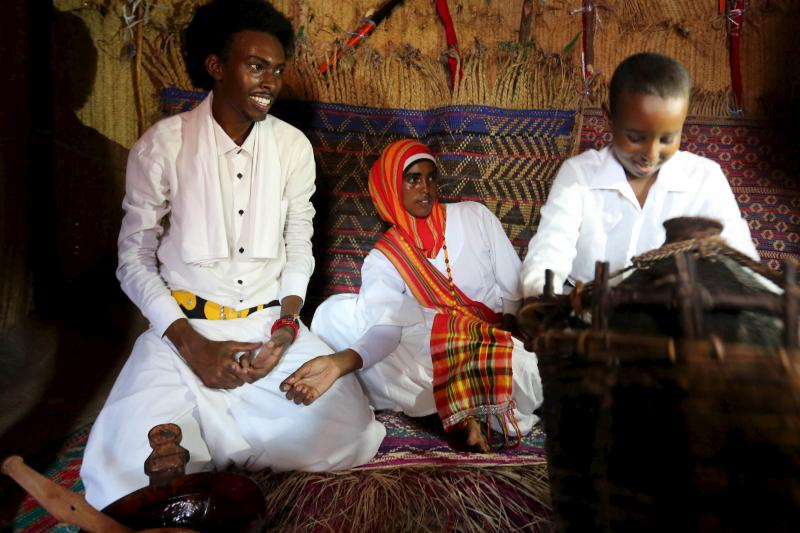 A Somali family sits inside a traditional house during an event to showcase traditional Somali culture in Hamarweyne district in the capital Mogadishu, December 3, 2015.