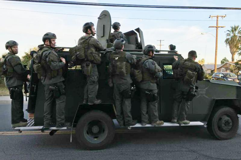 A police SWAT team conducts a manhunt after a mass shooting in San Bernadino, California December 2, 2015.