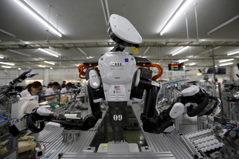 A humanoid robot works side by side with employees in the assembly line at a factory in Japan, July 2015.