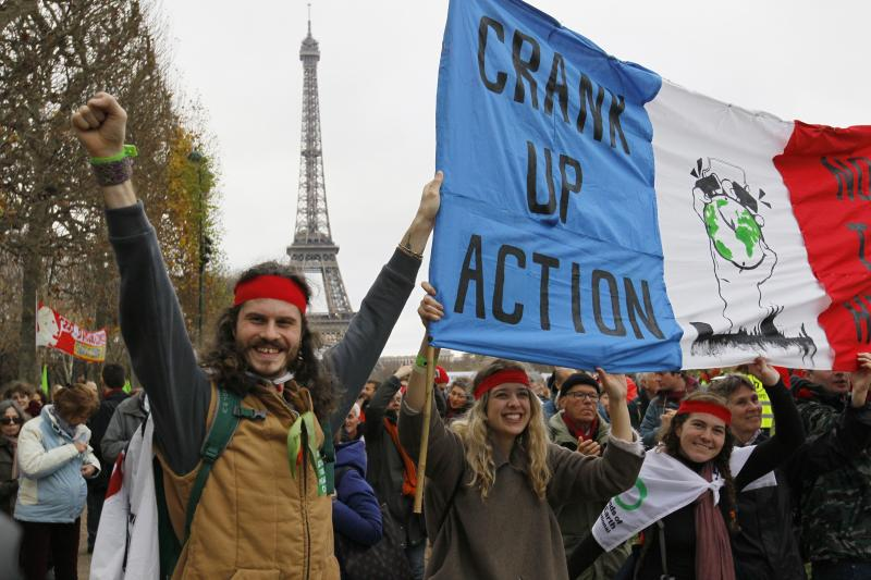 """Environmentalists hold a banner which reads, """"Crank up the Action"""" at a protest demonstration near the Eiffel Tower in Paris, France, December 12, 2015."""