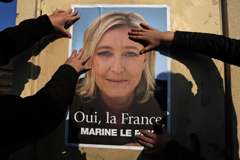 Supporters paste a poster of Marine Le Pen, France's National Front leader, on a wall before a political rally for local elections in Frejus March 18, 2014.
