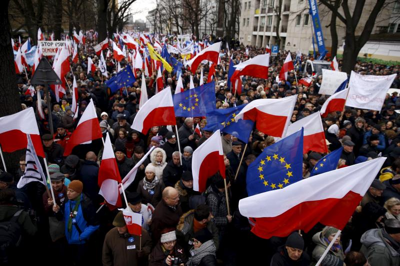 People hold European Union (EU) and Polish national flags during an anti-government demonstration in front of the Constitutional Court in Warsaw, Poland, December 12, 2015.