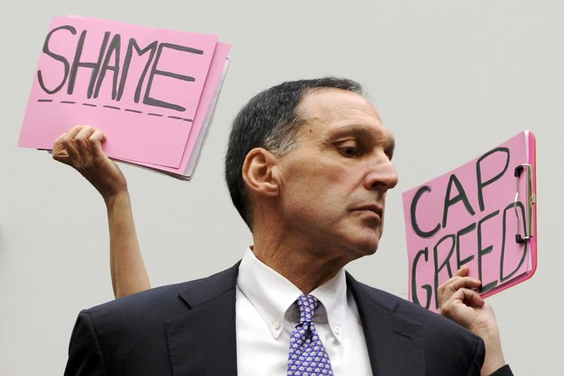 Protestors hold signs behind Richard Fuld, Chairman and Chief Executive of Lehman Brothers Holdings, as he takes his seat to testify at a House Oversight and Government Reform Committee hearing on the causes and effects of the Lehman Brothers bankruptcy.