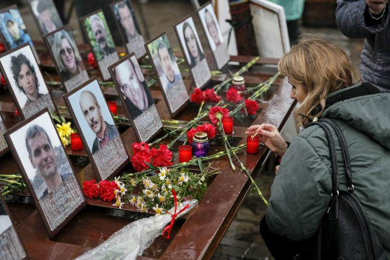 A woman takes part in a commemoration ceremony at the site where anti-Yanukovich protesters were killed during clashes in Kiev, Ukraine, November 21, 2015.