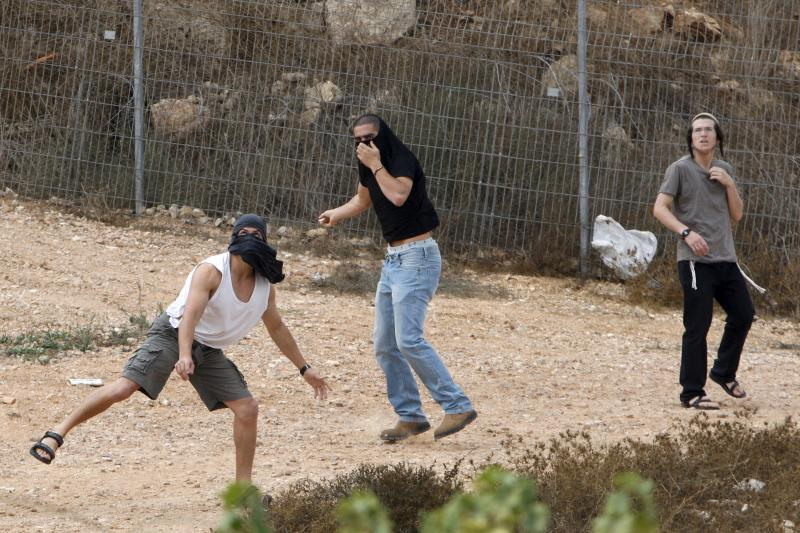 Israeli settlers throw stones at Palestinians in the West Bank city of Hebron after a wave of stabbings, October 2015.