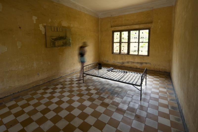 A woman walks into a torture chamber of the Tuol Sleng Genocide Museum, also known as the notorious Security Prison 21 (S-21), in the centre of Phnom Penh February 16, 2009.