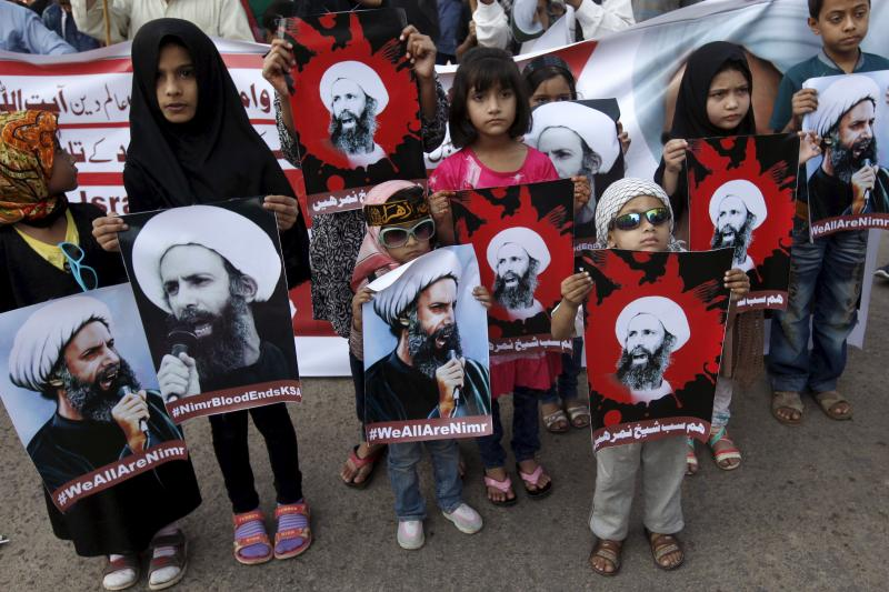 Shiite Muslim children hold pictures of Sheikh Nimr al-Nimr, who was executed along with others in Saudi Arabia, during a protest rally with others in Karachi, Pakistan, January 3, 2016.