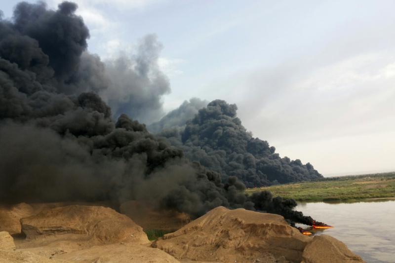 A cloud of smoke rises from an oil pipeline in Tikrit, north of Baghdad, April 17, 2014. A rusting pipeline that runs from the Kirkuk oilfields to the Baiji refinery in Salahuddin province leaked a large amount of oil into the Tigris River.