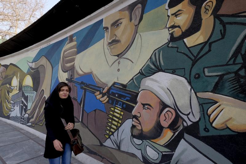 An Iranian woman walks past a revolutionary mural in Tehran, Iran, January 17, 2016.