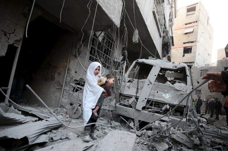 A girl carrying a baby inspects damage in a site hit by what activists said were airstrikes carried out by the Russian air force in the town of Douma, eastern Ghouta in Damascus, Syria, January 10, 2016.