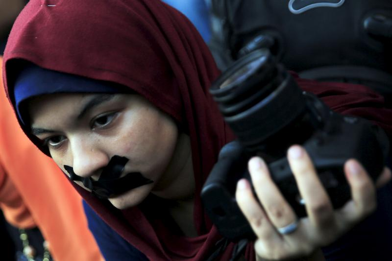 """A news photographer with her mouth taped holds up her camera during a protest against the detention of Ahmed Ramadan, a photojournalist with Egyptian private newspaper """"Tahrir,"""" in front of the Syndicate of Journalists in Cairo, Egypt, August 17, 2015."""
