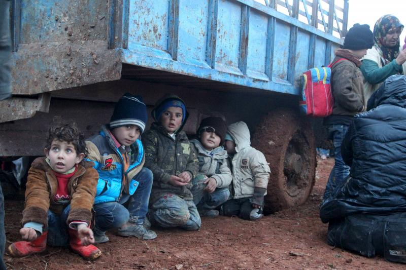 Displaced children, who fled with their families the violence from Islamic State-controlled area of al-Bab, wait as they are stuck in the Syrian village of Akda to cross into Turkey, January 23, 2016.