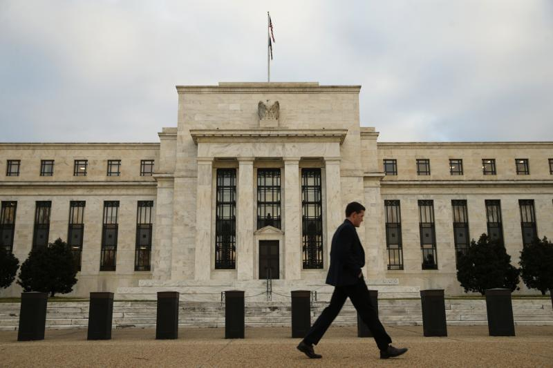 A man walks past the Federal Reserve in Washington, just before the U.S. central bank raised its interest rate, December 2015.