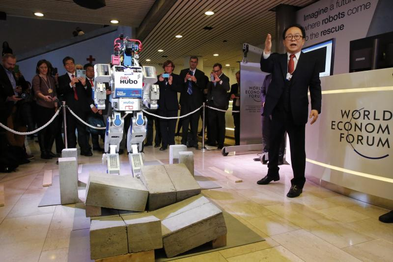 HUBO, a multifunctional walking humanoid robot performs a demonstration of its capacities next to its developer Oh Jun-Ho, Professor at the Korea Advanced Institute of Science and Technology (KAIST) during the annual meeting of the World Economic Forum (W
