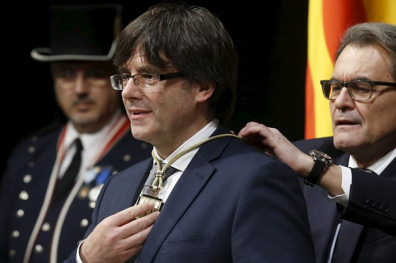 New President Carles Puigdemont of Catalunya receives a medal from outgoing Catalan President Artur Mas during Puigdemont's swearing-in ceremony in Barcelona, Spain, January 12, 2016.
