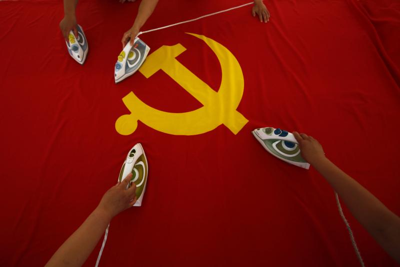 To prepare for the 90th anniversary of China's Communist Party, workers use irons to smooth out a Communist Party flag, Beijing, 2011
