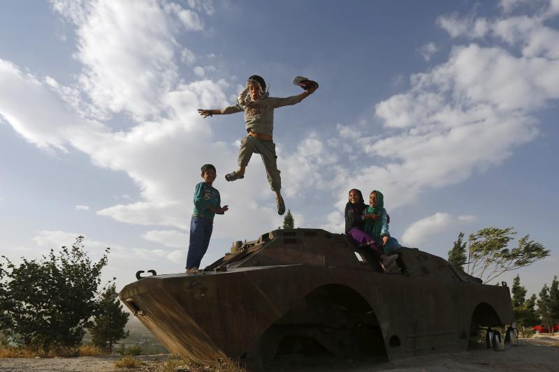 Afghan children play on the wreckage of an old Soviet armored vehicle in Kabul, Afghanistan, June 14, 2015.