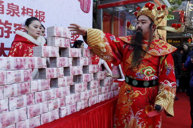 A man dressed as Chinese God of Fortune tries to reach a bundle of 100-yuan banknotes during an event held to celebrate the upcoming Spring Festival, at a park in Hangzhou, Zhejiang province, China, January 26, 2016.