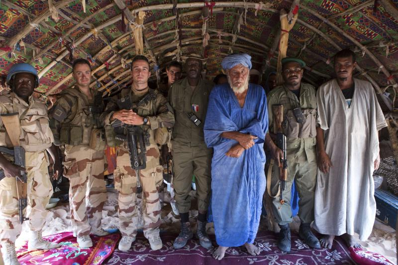 French and Malian soldiers pose with a village chief north of Timbuktu, November 2014. Many French officials believe that instability in the Sahel is the result of weak or fragile states' inabilities to control vast portions of their territories.