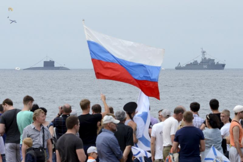 People gather to watch celebrations for Navy Day, with a Russian warship and a submarine seen in the background, in the far eastern city of Vladivostok, Russia, July 26, 2015.