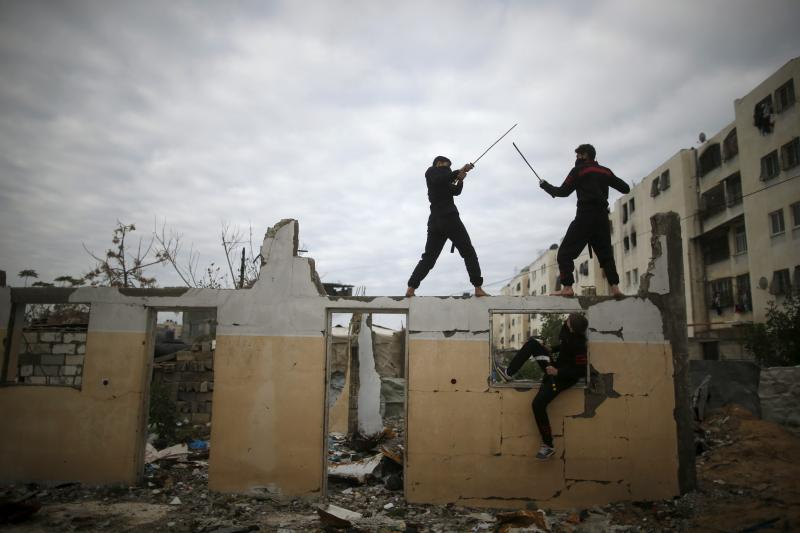 Palestinian youths fight with swords as they demonstrate their ninja-style skills for the photographer at the ruins of a house that was destroyed in 2014 war, in the northern Gaza Strip, January 29, 2016.