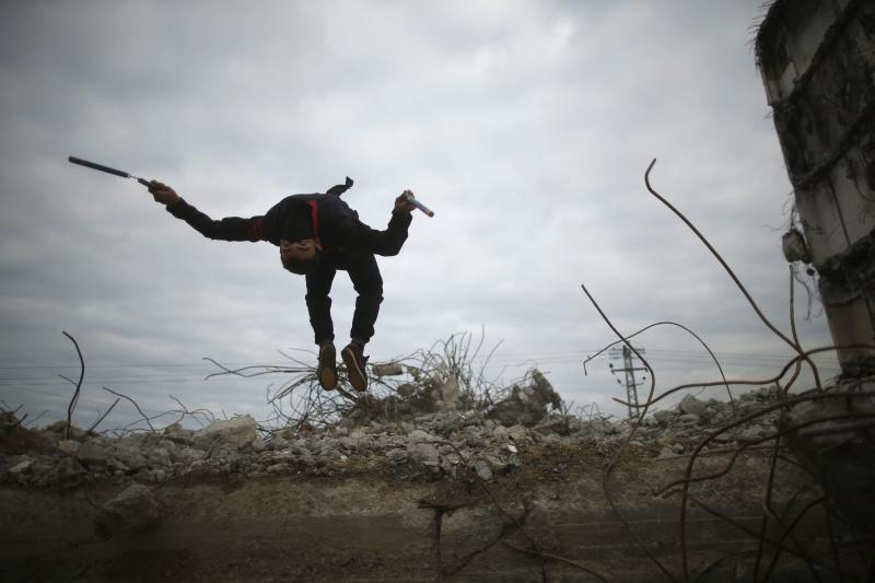 A Palestinian youth jumps as he demonstrates his ninja-style skills for a photographer at the ruins of a building that was destroyed in the 2014 war, in the northern Gaza Strip, January 29, 2016.