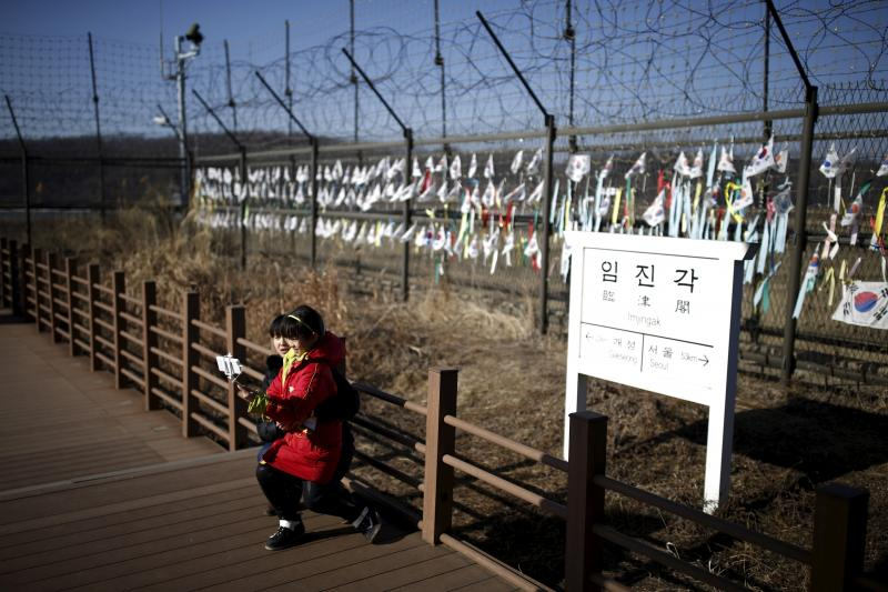 A woman takes photographs with her child in front of a sign showing the distance to North Korea's Gaeseong, also known as Kaesong, near the demilitarized zone separating the two Koreas in Paju, South Korea, February 7, 2016.