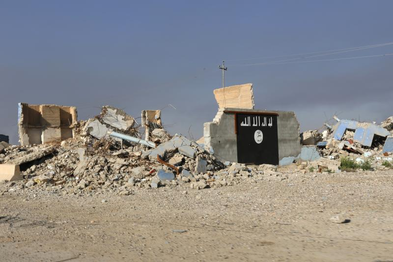 A destroyed building, with a wall painted with the black flag commonly used by Islamic State militants