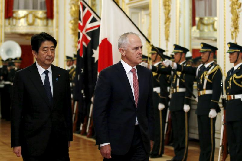 Australian Prime Minister Malcolm Turnbull and Shinzo Abe (L) review a guard of honor in Tokyo, Japan, December 2015.