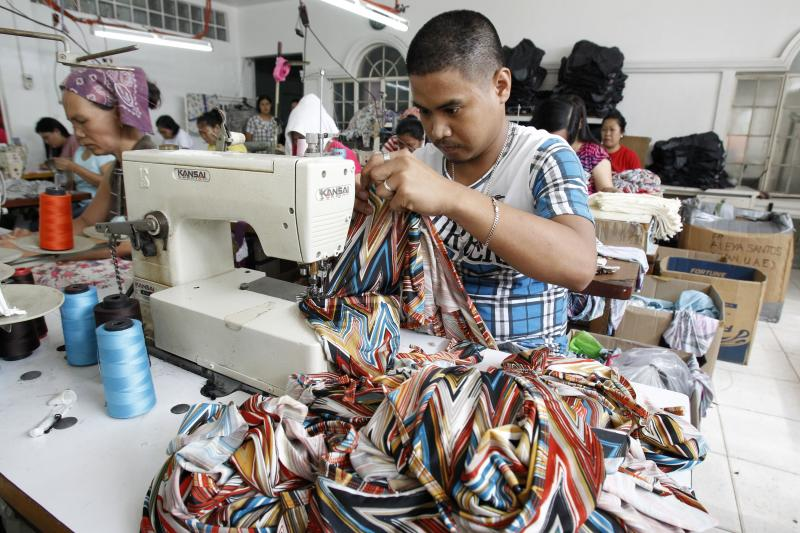 A garment worker sews a maternity dress at a factory east of Manila, Philippines. The labor force is still growing rapidly in the Philippines.