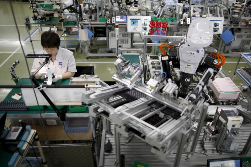 A humanoid robot works alongside an employee at a factory in Kazo, Japan, July 2015. Japan has negative real interest rates, an undervalued currency, and a high debt-to-GDP ratio, but it is a rich and stable country.