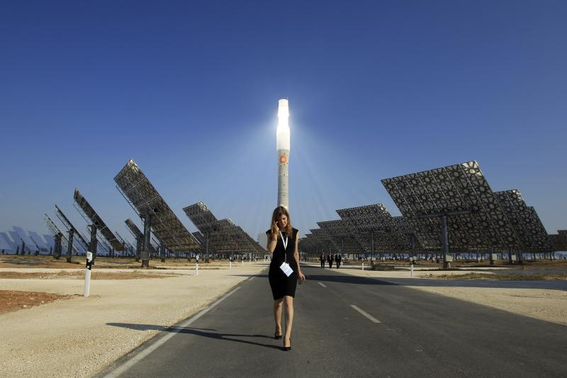 A woman walks near a solar power plant in Fuentes de Andalucia, Spain, October 2011. Installing solar panels boosts GDP initially, but thereafter the savings in oil or gas will reduce GDP.