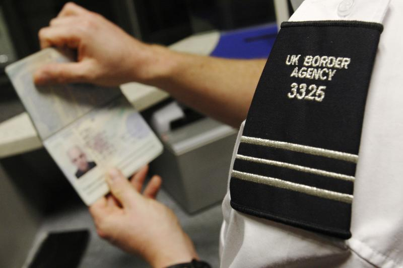 A UK Border Agency worker holds a passport at the North Terminal of Gatwick Airport near London, November 2009.