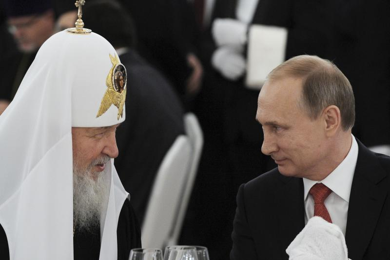 Russian President Vladimir Putin listens to Patriarch of Moscow and all Rus' Kirill during a reception commemorating the 1,000th anniversary of the death of Vladimir the Great at the Kremlin in Moscow, Russia, July 28, 2015.