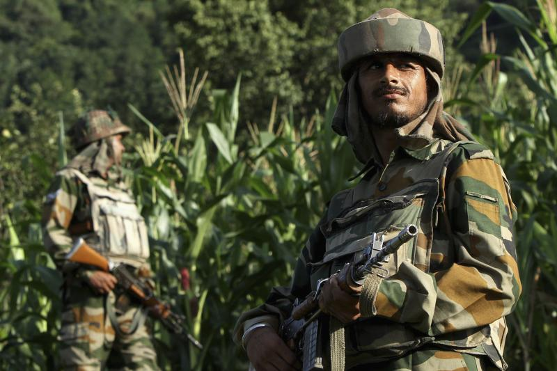 Indian army soldiers patrol near the Line of Control, a ceasefire line dividing Kashmir between India and Pakistan, in Poonch district, August 2013.