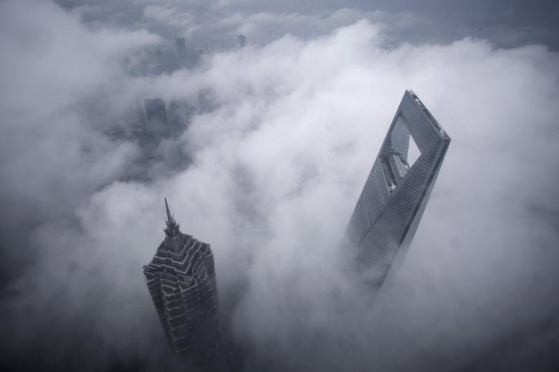 Skyscrapers Shanghai World Financial Center (R) and Jin Mao Tower are seen during heavy rain at the financial district of Pudong in Shanghai, May 15, 2015.
