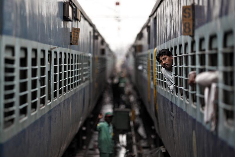 A passenger looks through the window of a train as he waits for electricity to be restored at a railway station in New Delhi, July 31, 2012.