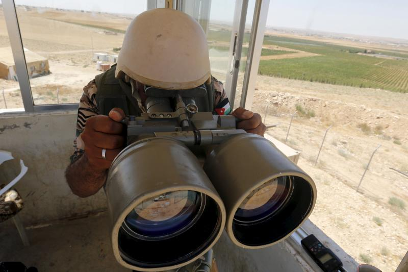 A soldier uses a pair of binoculars at a watchtower at the Jordanian-Syrian border, near Mafraq, August 16, 2015.