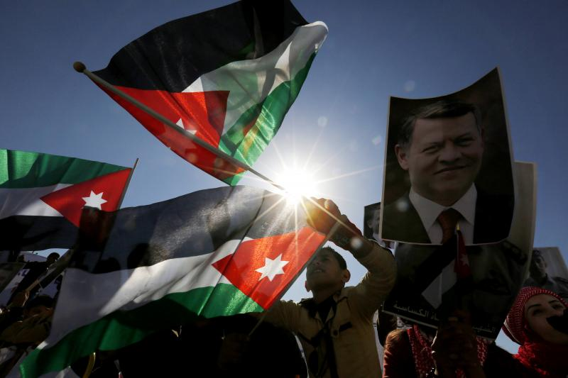 Protesters hold up pictures of Jordanian King Abdullah and pilot Muath al-Kasaesbeh with national flags, as they chant slogans during a rally in Amman to show their loyalty to the King and against ISIS, February 5, 2015.