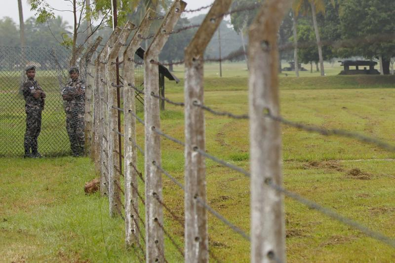 Two soldiers stand near a fence at a Sri Lankan air force base in Mannar, December 20, 2010.