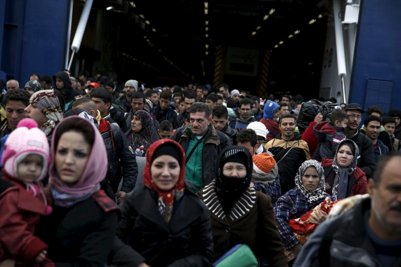 Refugees and migrants arrive aboard the passenger ferry Blue Star Patmos from the island of Lesbos at the port of Piraeus, near Athens, Greece, October 29, 2015.