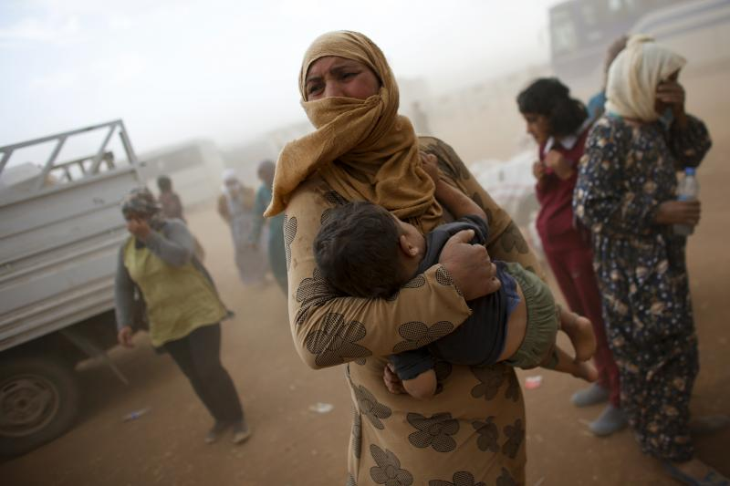 A Kurdish Syrian refugee waits for transport during a sand storm on the Turkish-Syrian border near the southeastern town of Suruc in Sanliurfa province, September 24, 2014.