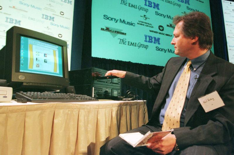 Paul Rettig of International Business Machines demonstrates a new system which allows home computer users to download music via the World Wide Web at a press conference in New York February 8, 1999.