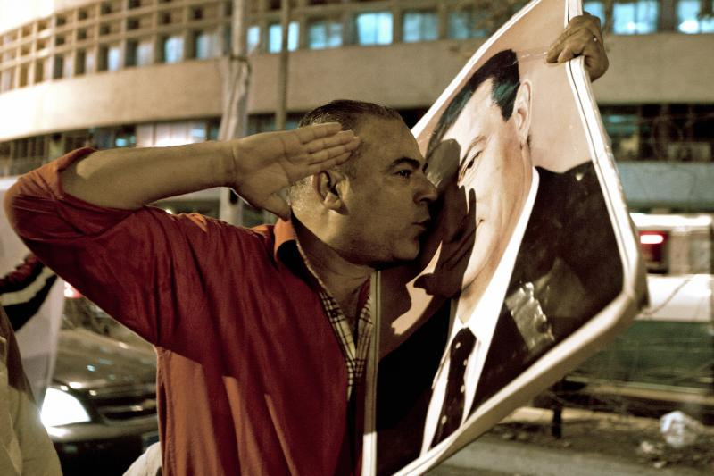 A supporter of former president Hosni Mubarak kisses a poster of Mubarak in downtown Cairo, April 17, 2011.