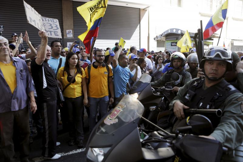 Supporters of Venezuela's opposition face motorized police officers who are blocking a street leading to the National Assembly in Caracas, January 2016.