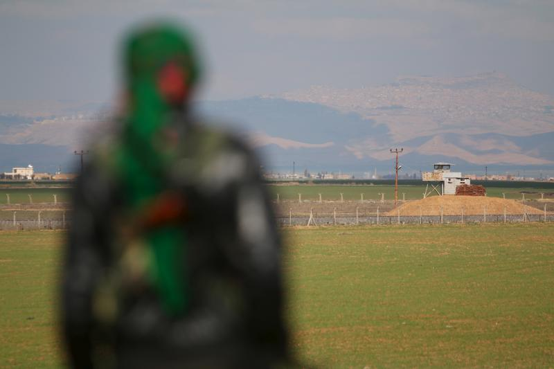 A Kurdish member of the Self-Defense Forces stands near the Syrian-Turkish border in the Syrian city of al-Derbasiyah, February 9, 2016.