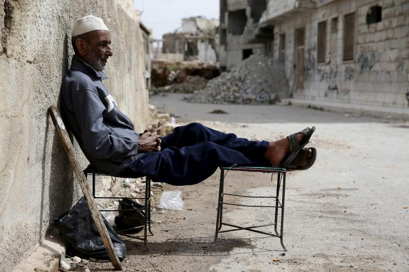 Khaled Kassmou, 70, sits along a street in the rebel held Qaboun neighborhood of Damascus, Syria, March 13, 2016.