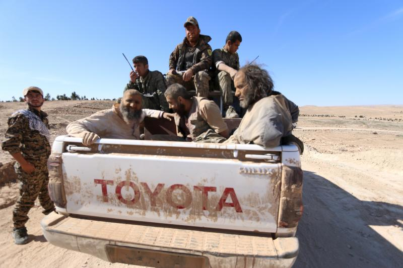 Three men that Democratic Forces of Syria fighters claimed were ISIS fighters sit on a pick-up truck while being held as prisoners, near al-Shadadi town, Hasaka countryside, Syria, February 18, 2016.