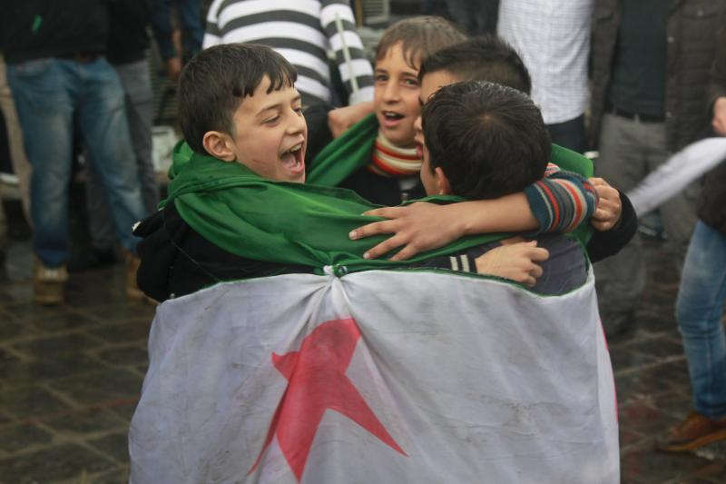 Children covering themselves with an opposition flag dance as they take part in a protest marking the fifth anniversary of the Syrian crisis in the old city of Aleppo, Syria, March 15, 2016.