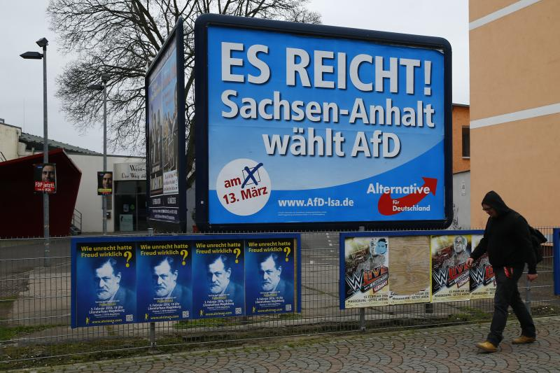 A man walks past an election poster of the right-wing Alternative for Germany (AfD) party reading 'That's enough! Saxony-Anhalt votes AfD' in the city of Magdeburg in Saxony-Anhalt, Germany, March 13, 2016.